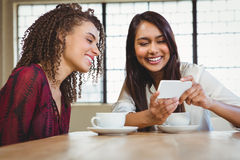 Female friends having coffee and looking at a smartphone Stock Image