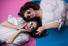 Female Friends Having Fun. Sunglasses cute crazy playful isolated on colorful background Royalty Free Stock Image