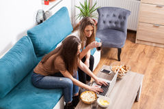 Female friends having party and looking at laptop Royalty Free Stock Photos