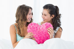 Female friends with heart shaped pillow in bed Stock Image