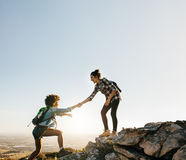Female friends hiking help each other in mountains. Young female hiker helping friend while trekking in mountain Stock Photos