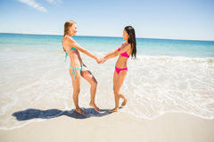 Female friends holding hands on beach Royalty Free Stock Image
