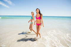Female friends holding hands on beach Stock Photo