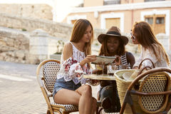 Female friends on holiday reading a guidebook outside a cafe Stock Photo