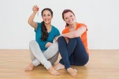 Female friends with house keys sitting on the floor Stock Photos