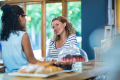 Female friends interacting with each other at counter. In caf Royalty Free Stock Photography