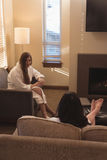 Female friends interacting with each other in the living room. At home Stock Photography