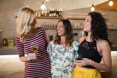 Female friends interacting while having drink at counter. In restaurant Stock Photo