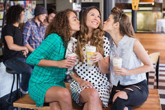 Female friends kissing woman in restaurant Stock Photo