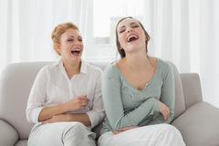 Female friends laughing while sitting on sofa in the living room Royalty Free Stock Image