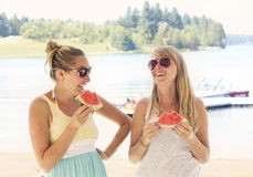 Female Friends laughing together at outdoor picnic. Two female friends eating together and laughing together at an outdoor picnic by the lake. Enjoying the Royalty Free Stock Photos