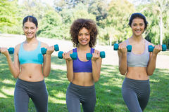 Female friends lifting dumbbells Royalty Free Stock Images