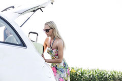 Female friends loading luggage in car trunk against clear sky Royalty Free Stock Photography