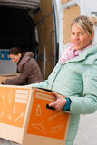 Female friends loading a moving truck. Two young women loading into a moving truck, they carry moving boxes Royalty Free Stock Images