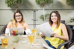 Female friends looking at restaurant menu Stock Photography
