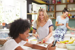 Female Friends Making Breakfast Whilst Checking Mobile Phone Royalty Free Stock Image