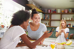Female Friends Making Breakfast Whilst Checking Mobile Phone Stock Photo