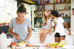 Female Friends Making Breakfast Whilst Checking Mobile Phone Stock Image