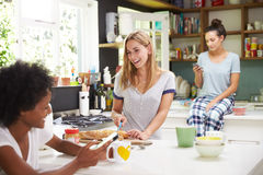 Female Friends Making Breakfast Whilst Checking Mobile Phone Royalty Free Stock Photo
