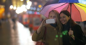 Female friends making selfie under rainbow. Two happy women making phone selfie under colorful umbrella during their friendly evening walk in the rainy city stock video footage