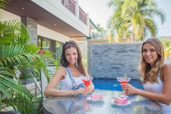 Female friends in outdoor cafe. Female friends sitting in outdoor cafe with cocktail and cake enjoying summer tropical vacation Royalty Free Stock Photography