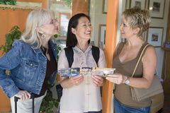 Female Friends With Pamphlet Of Resort. Three female friends communicating while holding pamphlet of resort stock photos