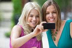 Female Friends Photographing Themselves Royalty Free Stock Photos