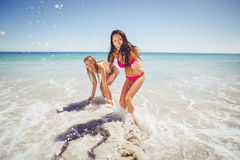 Female friends playing on beach Stock Image