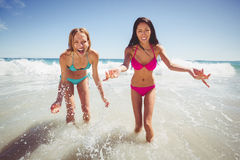 Female friends playing on beach Stock Images