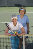 Female Friends Playing Doubles At The Tennis Court royalty free stock photos
