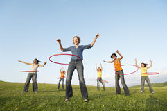 Female Friends Playing With Hula Hoop Against Sky In Park