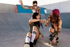 Female friends playing with skateboard at skate park. Group of women enjoying riding skateboards at skate park Royalty Free Stock Photos
