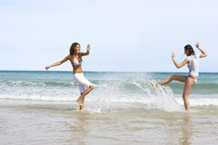Female Friends Playing In Water At Beach Royalty Free Stock Photos