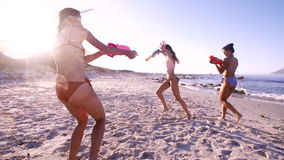 Female friends playing with water guns on the beach stock video footage