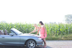 Female friends reading map on convertible against clear sky Royalty Free Stock Images