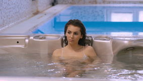 Female friends relaxing in jacuzzi, speaking and smiling stock video