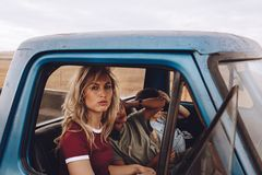 Female friends on road trip traveling by a car royalty free stock photography