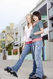 Female Friends Rollerblading On Street Royalty Free Stock Photo