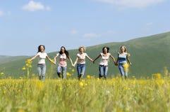 Female Friends Running Against Mountain Range Stock Images
