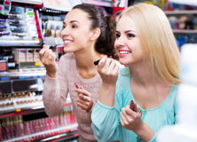 Female friends selecting lip gloss Royalty Free Stock Image
