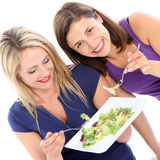 Female friends sharing a plate of salad Stock Photos