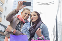 Female friends with shopping bags taking photos through mobile phone Royalty Free Stock Photography