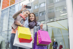 Female friends with shopping bags taking self portrait through mobile phone against store Royalty Free Stock Photos