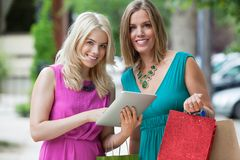 Female Friends With Shopping Bags Using Digital Royalty Free Stock Image
