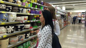 Female friends with shopping bags walking in the supermarket. Two womens with shopping in the store stock footage