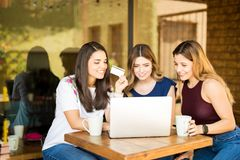 Female friends shopping online at cafe. Group of young women using laptop with credit card in hand, doing online shopping at restaurant stock image