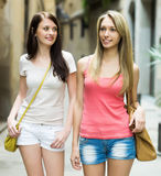 Female friends in shorts having city tour at vacation Royalty Free Stock Image