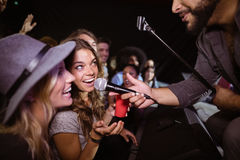 Female friends singing with male singer at nightclub Stock Photo