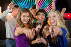Female friends singing song together in bar. Portrait of smiling female friends singing song together in bar Royalty Free Stock Photography