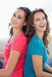 Female friends sitting back to back in living room Stock Photography